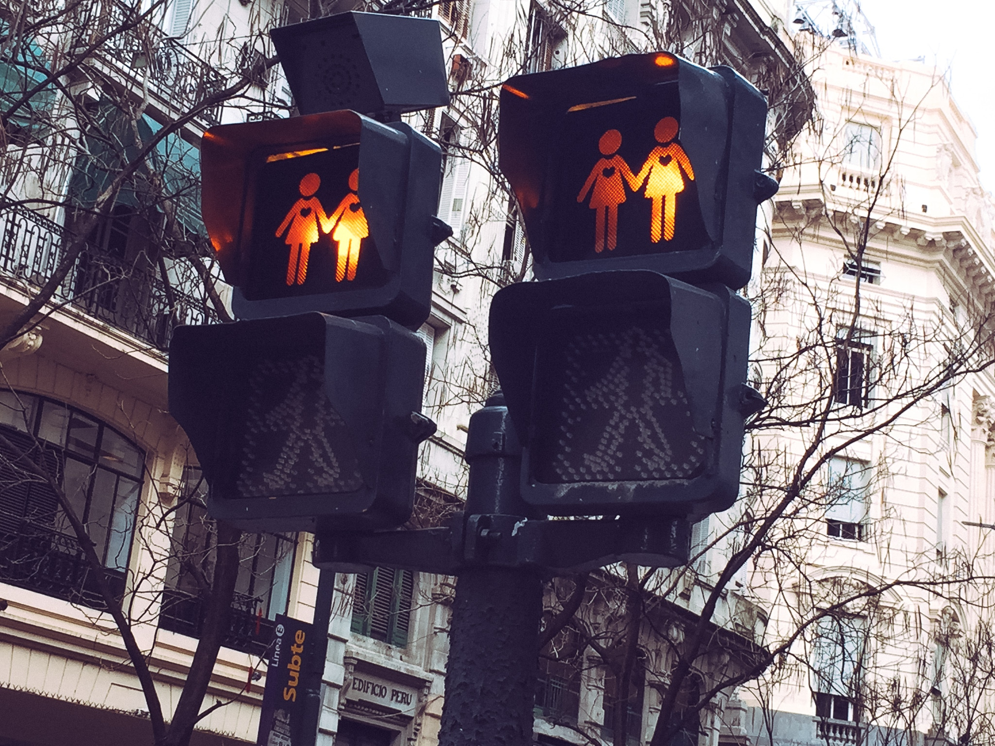 A stoplight with two same-gender couples lit in red.